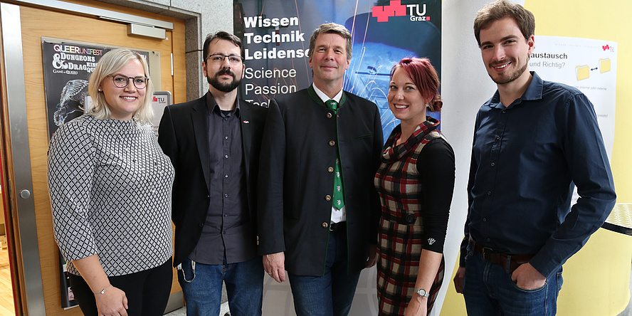 "Fair-haired young woman with glasses, dark-haired young man with beard and glasses, greying man in a Styrian jacket, young woman with reddish hair and young man with brown beard in front of a banner bearing the title ""Wissen, Technik, Leidenschaft"""
