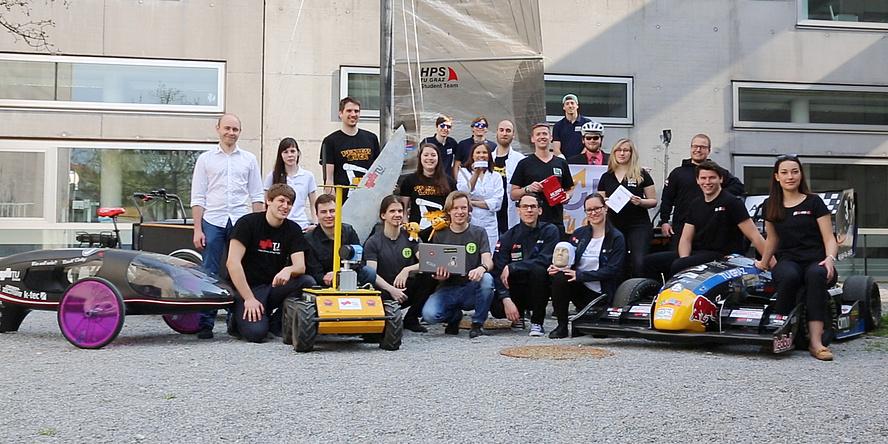 Gemeinschaftsbild von Studierenden aus Teams der TU Graz mit Rennautos, Roboter, Segeljolle und mehr.