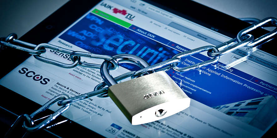 A tablet in the background, on which the website of the Institute for Applied Information Processing and Communication Technologies is open, with a chain with padlock in front