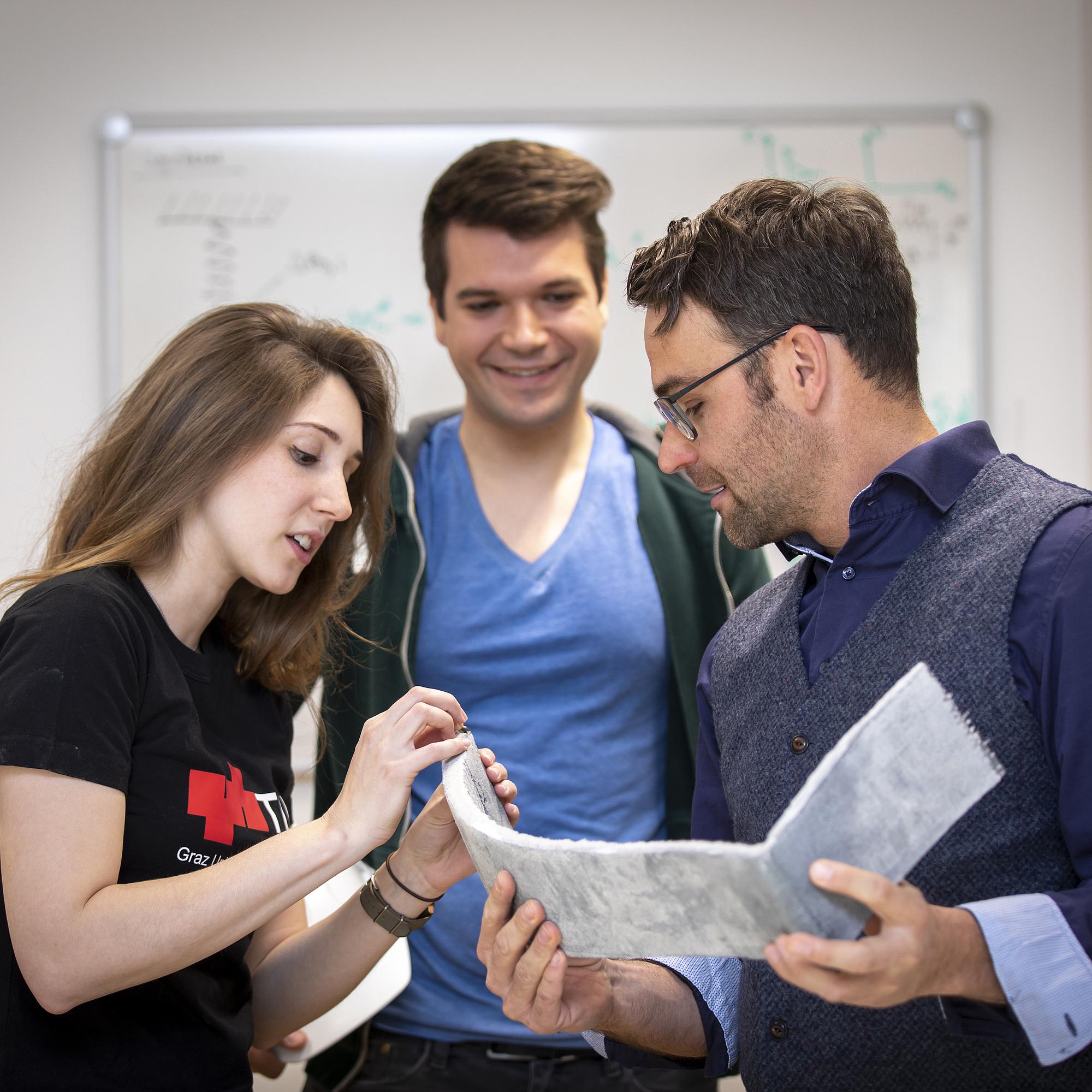 Ein Lehrender und zwei Studierende besprechen ein Bauteil.