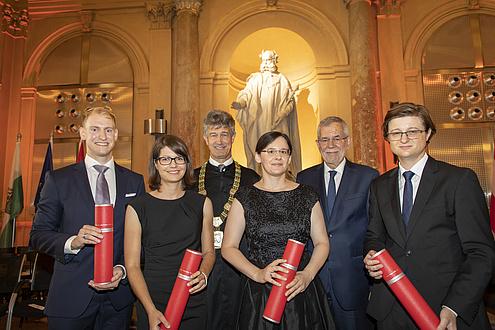 Zwei Frauen und vier Männer stehen nebeneinander, vier von Ihnen halten rote Rollen in der Hand.