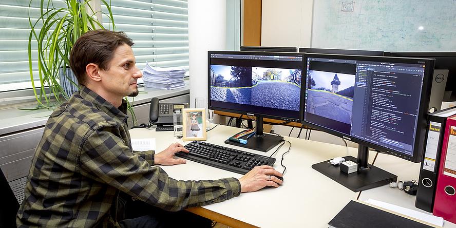 Mann sitzend am Schreibtisch vorm Computer