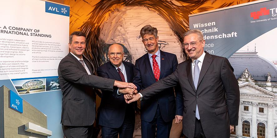 Vier Herren in Anzügen stehen vor den beiden Roll Ups der AVL und der TU Graz und kreuzen die Hände