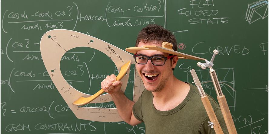 Ein lachender Mann im grünen T-Shirt steht vor einer grünen Tafel, auf der mathemaitsche Formeln geschrieben stehen und hält einen überdimensionalen Zirkel und eine Schablone für Kegelschnitte in den Händen.