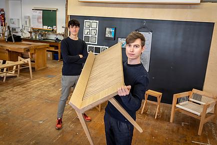 Zwei Architekturstudierende mit Bank in der TU Graz-Holzwerkstatt