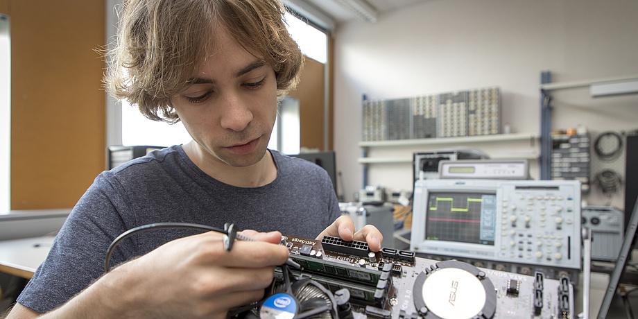 Ein blonder junger Mann sitzt an einem Tisch und arbeitet am Innenleben eines Computers.