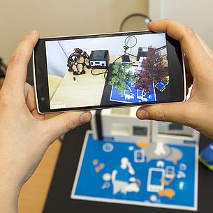 Zwei Hände halten einen Handy, auf dem Bildschirm sieht man Modelle, die auf einem Schreibtisch stehen.