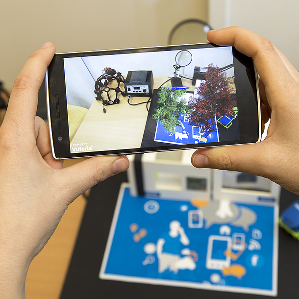 Two hands hold a mobile phone, on the screen you can see models standing on a desk.