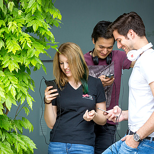 Zwei Männer und eine Frau blicken auf ihre Handys. Bildquelle: Lunghammer – TU Graz
