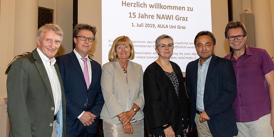 """Zwei Damen, links und rechts flankiert von jeweils zwei Männern stehen vor einer Videoleinwand, auf der """"Herzlich willkommen zu 15 Jahre NAWI Graz"""" zu lesen ist"""