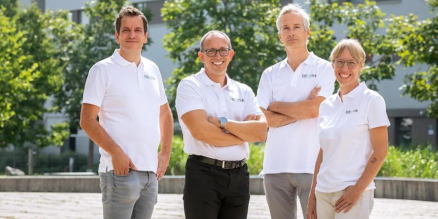 Vier Menschen mit weißen Poloshirts