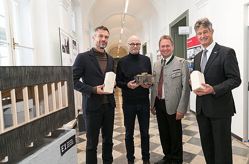 Vier Männer stehen vor einem Architketurmodell