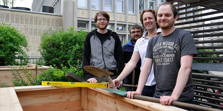 Die vier Helfer, die die Hochbeete aufgebaut haben, lachen mit Gartenwerkzeugen in der Hand in die Kamera.
