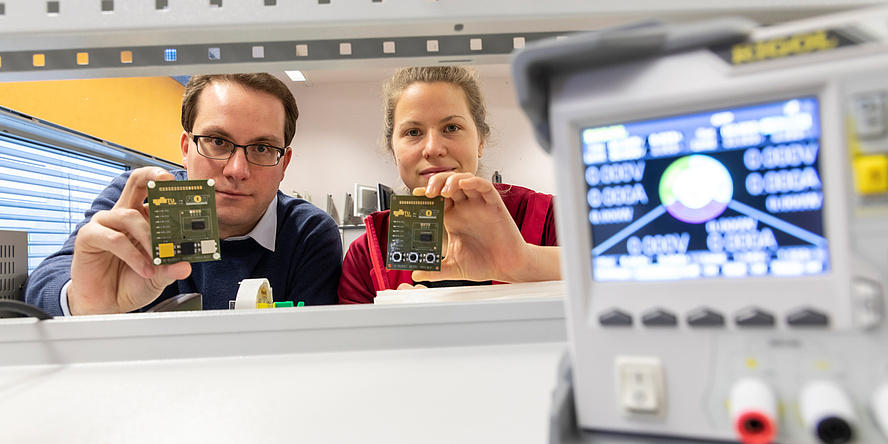 Researchers with electronic circuit boards in their hands