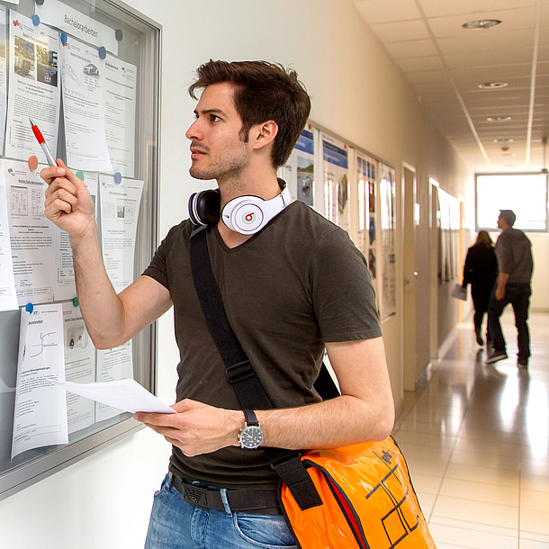 Young man standing in front of a board with information. Photo source: Lunghammer - TU Graz