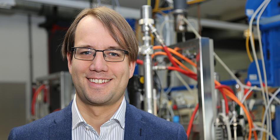 Ein blonder Mann steht vor bunter Laboreinrichtung.