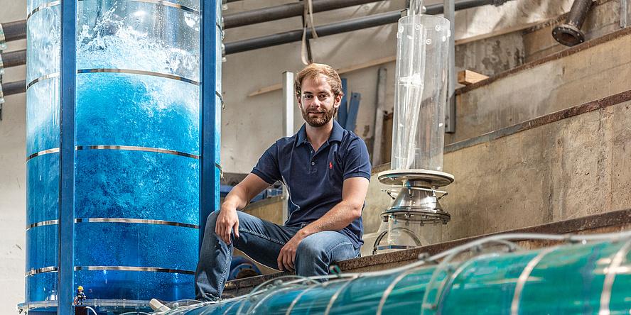 Ein junger Mann mit Bart in Jeans und blauem T-Shirt sitzt im Wasserbaulabor und ist umgeben von Versuchanordnungen in Form von wassergefüllten Plexiglas-Röhren