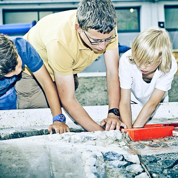 Zwei Schüler mit einem Studenten vor einem Modell mit Steinen. Bildquelle: Lunghammer – TU Graz