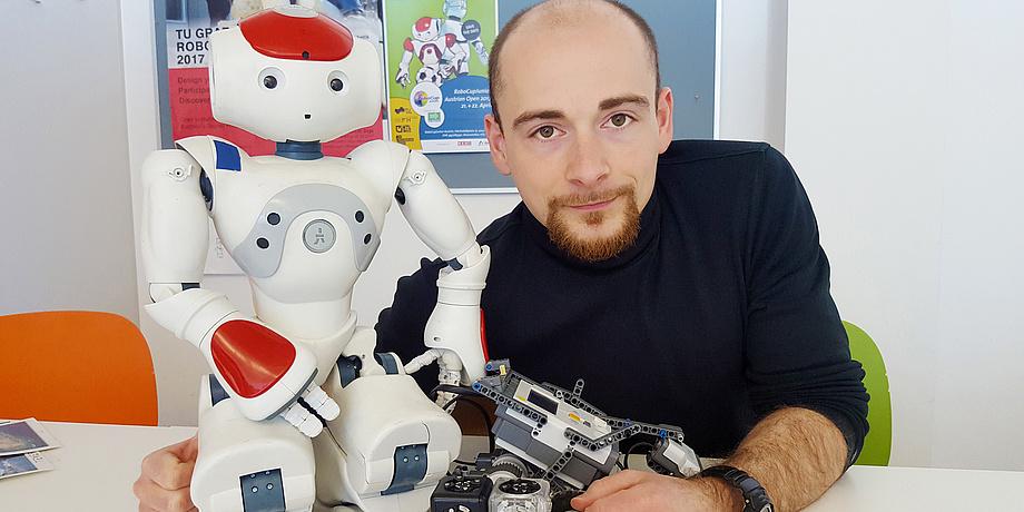 [Translate to Englisch:] Martin Kandlhofer mit drei Robotern: einem humanoiden weißen Nao, einem Legoroboter und einem Würfelroboter.
