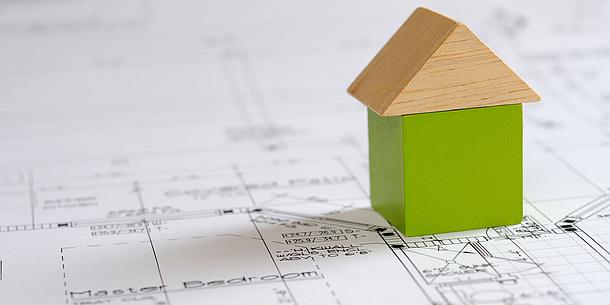 Ein Haus aus Bausteinen steht auf einem gezeichneten Plan. Bildquelle: Andrew Horwitz – iStockphoto.com