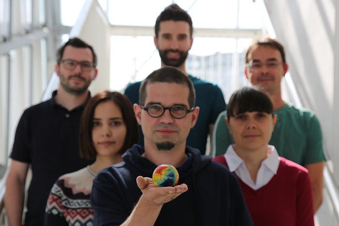 Mehrere Personen stehen in einer Gruppe hintereinander. Der Mann im Vordergrund hält eine Mini-Weltkugel auf der Handfläche.
