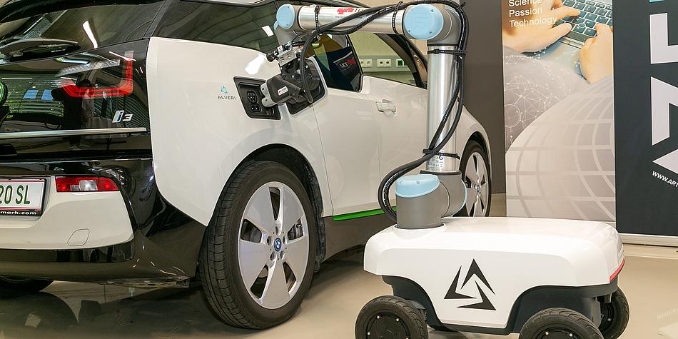 A car with an open fuel cap, next to it a robot arm