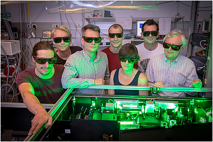 A group of researchers in the physics laboratory bathed in green light