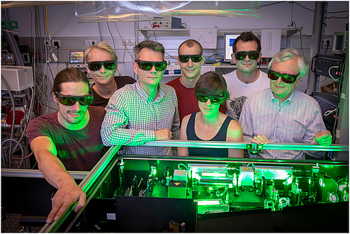 Eine Forschenden-Gruppe im Physik-Labor in grünes Licht getaucht