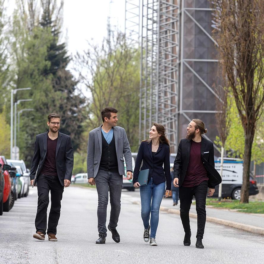 4 jungen Leute spazieren über den Campus