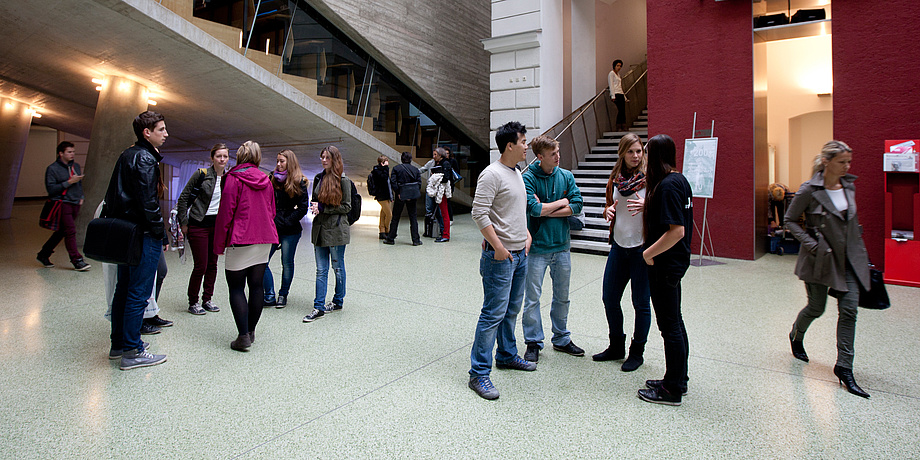 """Approx. 15 Studierende in smaller groups in front of Lecture Hall 1 at TU Graz' Campus """"Alte Technik""""."""