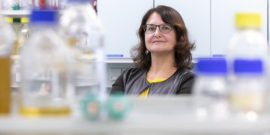 Gabriele Berg. Sie trägt braune Haare und eine Brille und steht in einem Labor.
