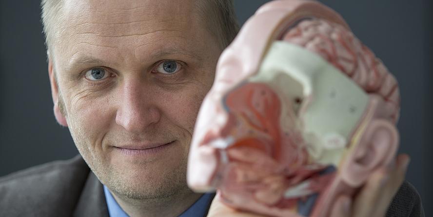 Ein blonder Mann, der eine Plastikabbildung eines Schädels in der Hand hält.