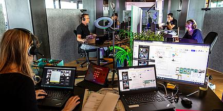 Menschen arbeiten konzentriert mit Headset und vor Computern