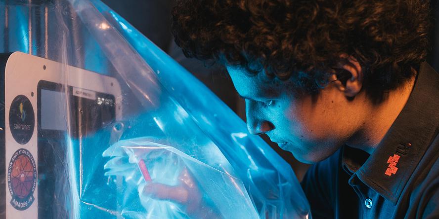 Ein junger Mann betastet durch eine Kunststoffhülle hindurch ein etwa fünf Zentimeter großes Bauteil.