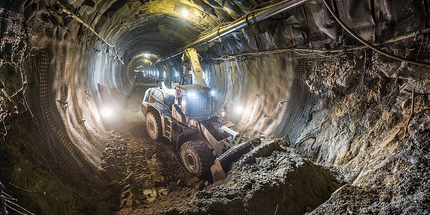 Ein Caterpillar Tunnelbagger schiebt in einem Tunnel Erde beiseite.