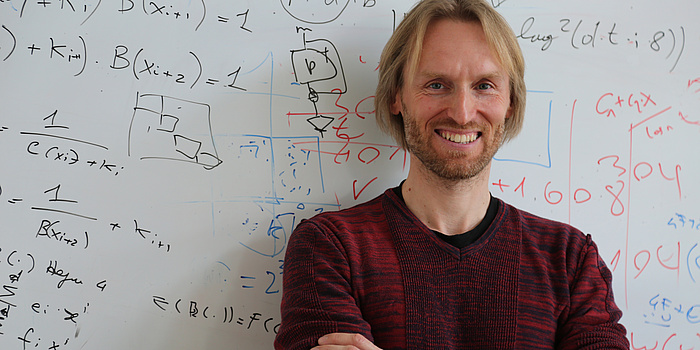 Ein blonder Mann mit rotem Pullover steht vor einem Whiteboard auf dem bunte Schrift zu sehen ist.