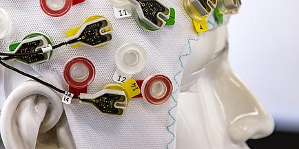 Das Model eines Kopfes mit einer EEG-Mütze und vielen Elektroden.