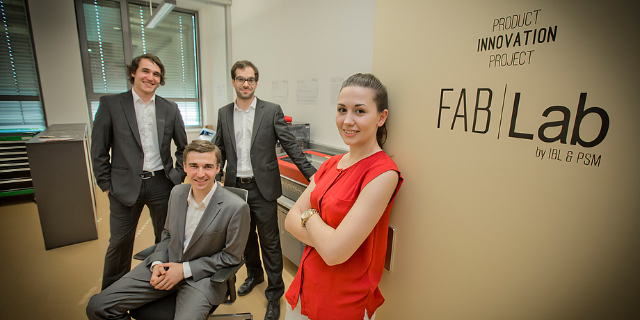 A Product Innovation Project team, three male and one female students in front of the FabLab of TU Graz.