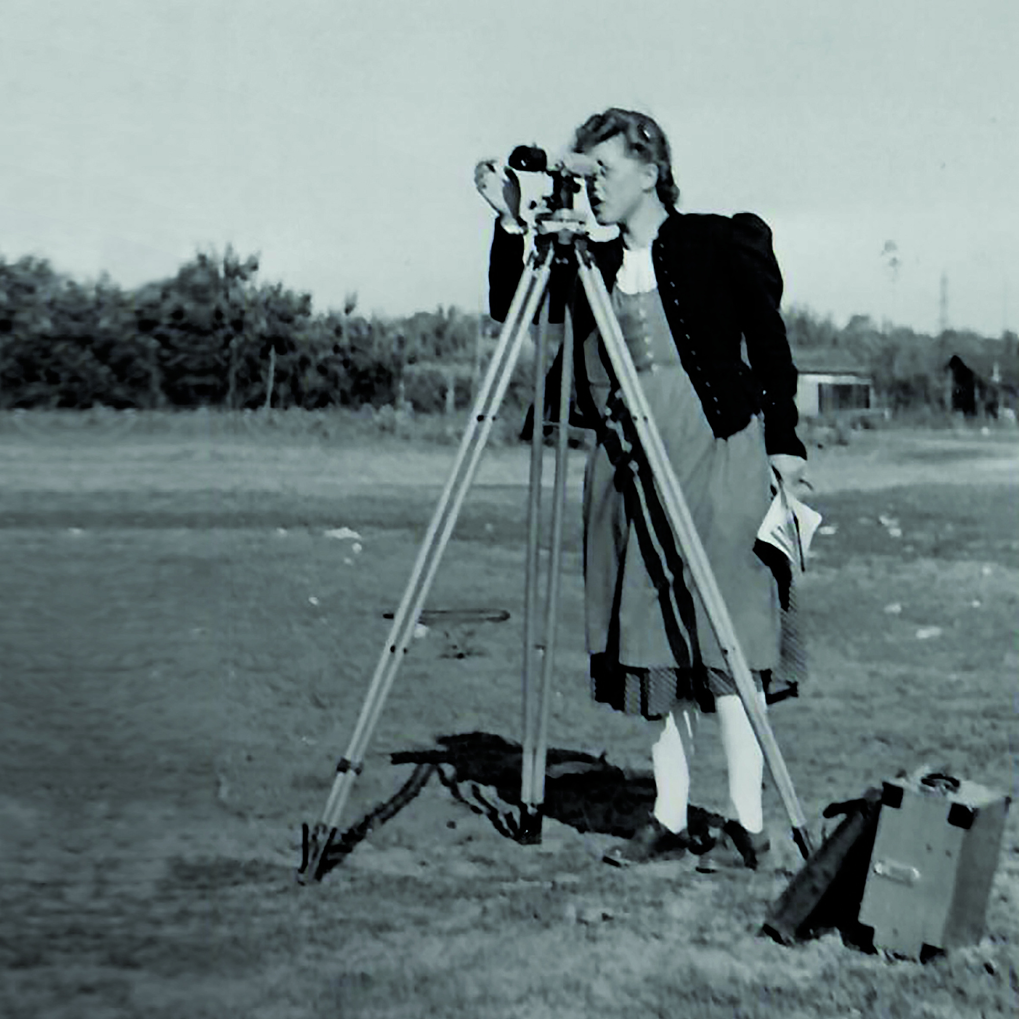 The black and white picture shows a woman at a surveying device.