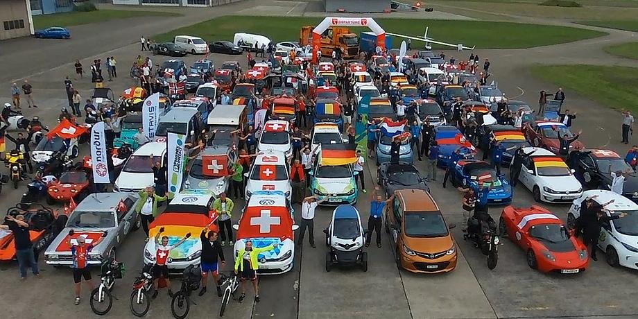 Unzählige Elektromobile von Autos über Bikes bis Scooter stehen auf einem grooßen Platz, teils geschmückt mit den Nationalflaggen der Teams.