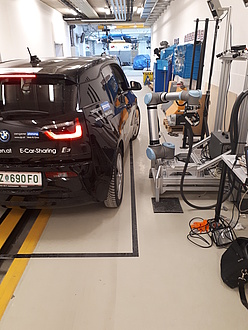 Ein blaues Elektrofahrzeug wird in einer Halle mittels des Roboterladesystems aufgeladen. Man sieht, dass das Fahrzeug eine nicht exakte Parkposition einnimmt.