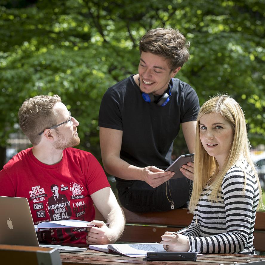 Zwei junge Männer im Gespräch, eine junge Frau blickt aus dem Bild