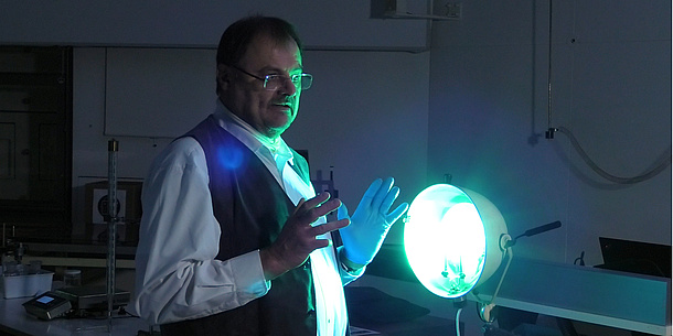 Ein Mann wird von einer grünlichen Lampe angestrahlt.
