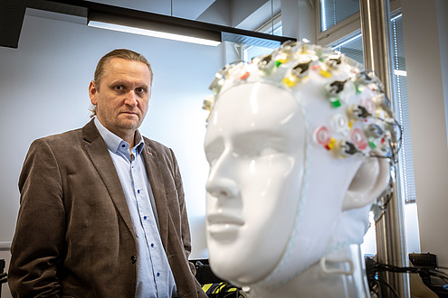 Mann mit Anzug neben einem Modell eines Kopfes, der eine EEG-Haube trägt