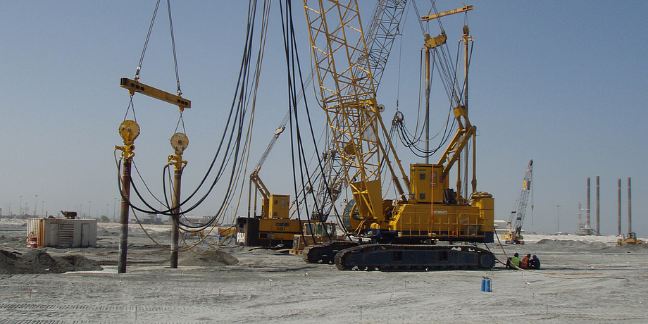 Große Baumaschinen und Geräte stehen auf Wüstensand. Der Boden wird bearbeitet. Der Himmel im Hintergrudn ist blau.