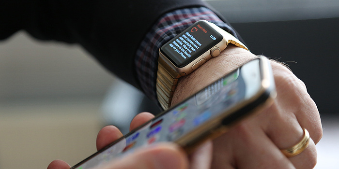 Two hands. One hand holds a Smartphone, the other a Smartwatch.
