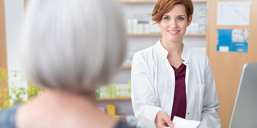 Eine Apothekerin mit weißem Mantel und roten Haaren reicht einer weißhaarigen Dame einen Zettel.