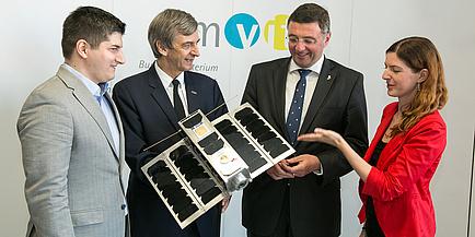 Drei Männer und eine Frau halten beziehungsweise betrachten den Kleinsatelliten OPSSAT.