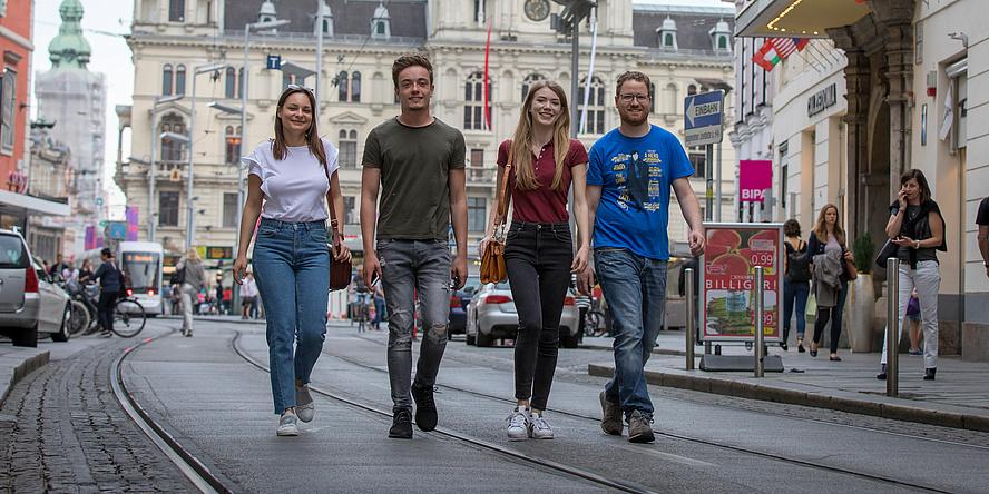 Zwei Studentinnen und zwei Studenten gehen vor dem Hintergrund des Grazer Hauptplatzes auf den Straßenbahnschienen dem Fotografen entgegen.