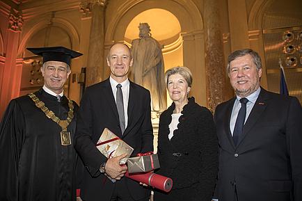Drei Männer und eine Frau stehen nebeneinander und lächeln. Einer der Männer hält eine rote Rolle in Händen.